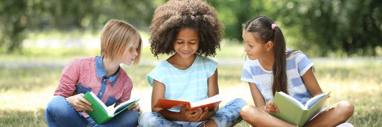 três meninas sentadas em roda lendo livros