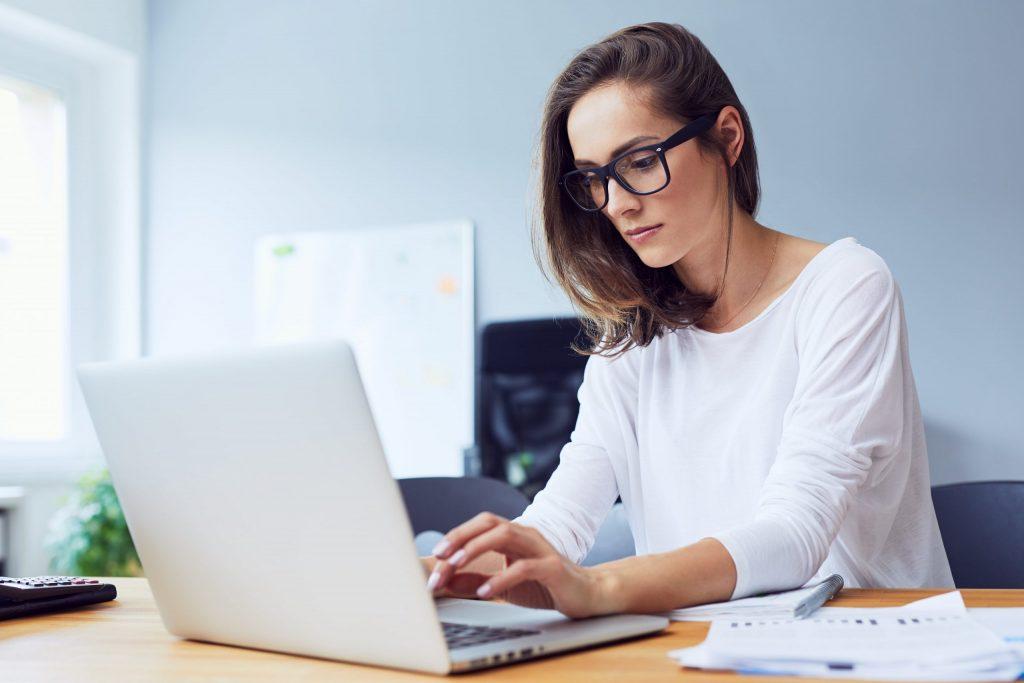 Mulher digitando em computador.